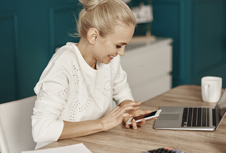 Cheerful woman reading text message at home office
