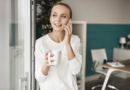 Cheerful woman with coffee talking by mobile phone