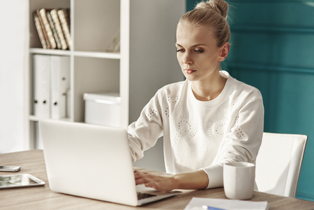 Serious woman with laptop working at home office   Stock Photo