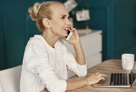 Multitasking businesswoman working at office Stock Photo