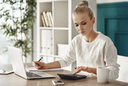 Concentrated woman budgeting at office  Imagens