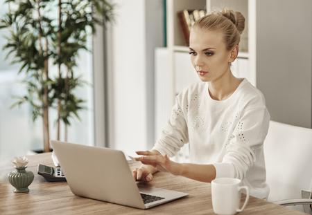 Blonde woman typing on laptop keyboard  Stock Photo