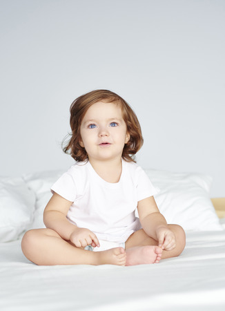 Child sitting on bed