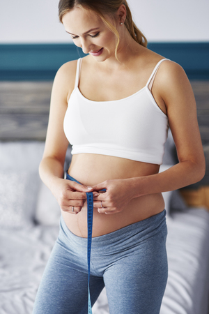 Cheerful pregnant woman measuring her belly at bedroom