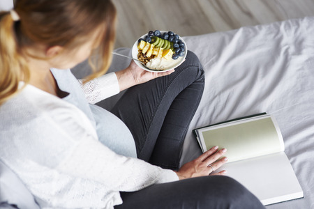 Top view of pregnant woman eating and reading a book