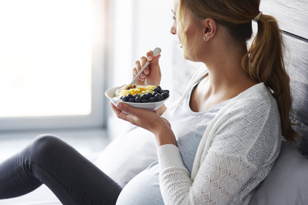 Side view of pregnant woman having breakfast at bedroom Stock Photo