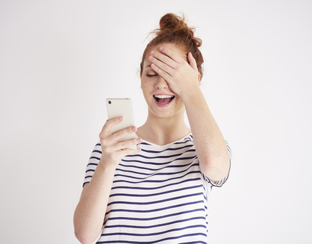 Girl using mobile phone and laughing at studio shot Фото со стока