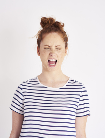 Portrait of woman with closed eyes shouting at studio shot Stock Photo