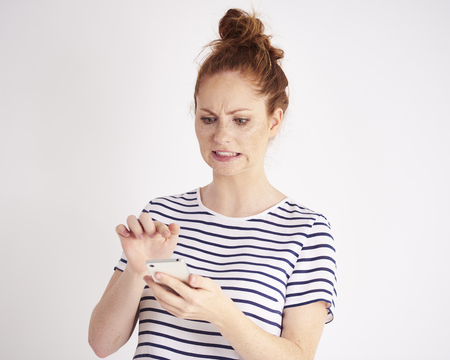 Embarrassed woman using a mobile phone at studio shot