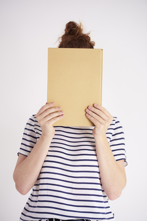 Young woman covering her face with book at studio shot