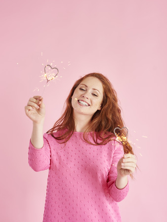 Portrait of cheerful woman holding heart shaped sparkler at studio