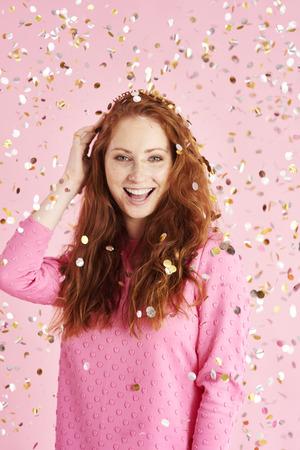 Portrait of cheerful woman among confetti at studio shot