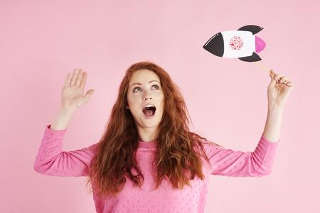 Young woman looking up and shouting at studio shot