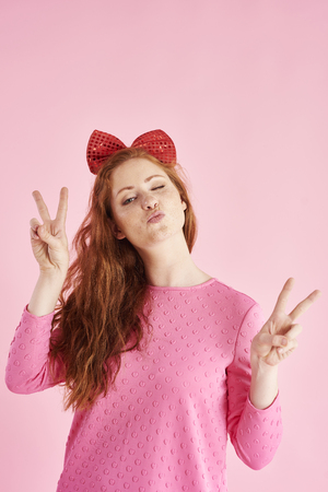 Peace sign made by young woman at studio shot Stock Photo