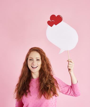Portrait of cheerful woman holding speech bubble at studio shot