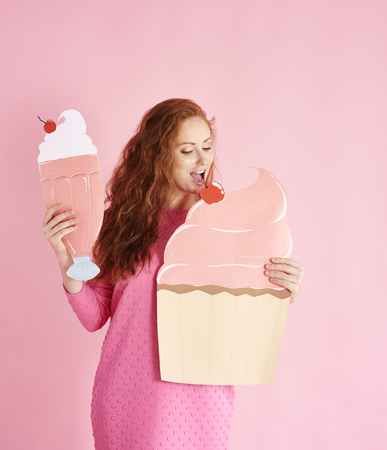 Young woman eating a cupcake at studio shot Stock Photo