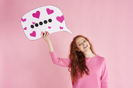 Portrait of cheerful woman holding thought bubble at studio shot Stock Photo