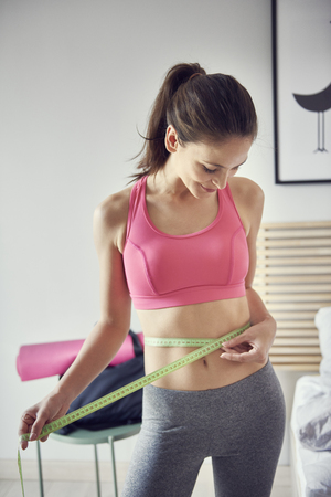 Slim woman measuring her waist at home