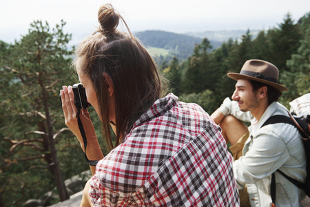 Young woman photographing mountain landscape Stock Photo