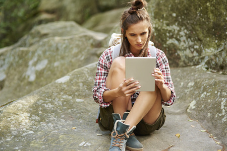 Backpacker using a tablet in the mountains Stock Photo