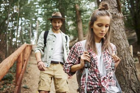 Front view of couple with backpacks walking through forest