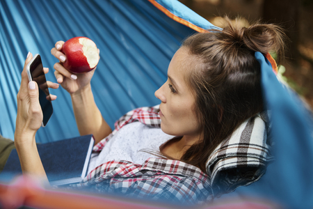Woman relaxing on hammock and using mobile phone 스톡 콘텐츠