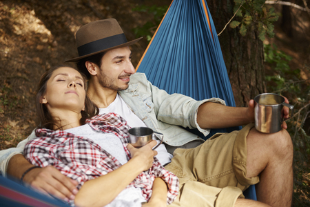 Couple in love relaxing on hammock in forest