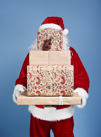 Santa Claus holding stack of christmas gifts