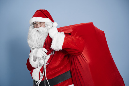 Tired santa claus carrying heavy sack 免版税图像
