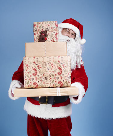 Portrait of santa claus holding stack of christmas presents Stock Photo