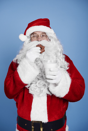 Hungry santa claus eating cookie at studio shot Stock Photo