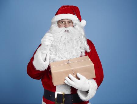 Surprised santa claus opening gift Stock Photo