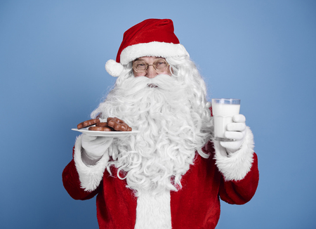 Santa claus with cookie and milk at studio shot Imagens