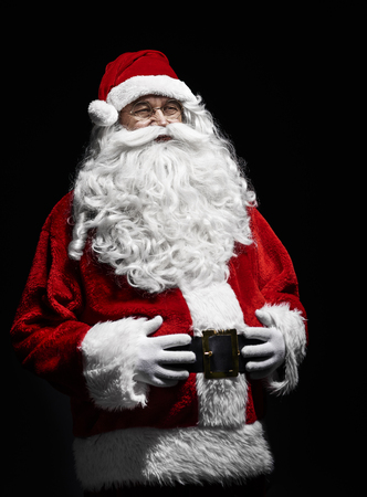 Portrait of cheerful santa claus with hands on stomach