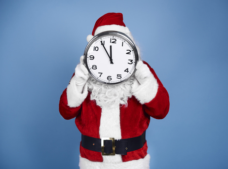 Santa Claus holding clock in front of his face