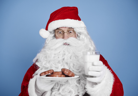 Surprised santa claus with milk and cookie