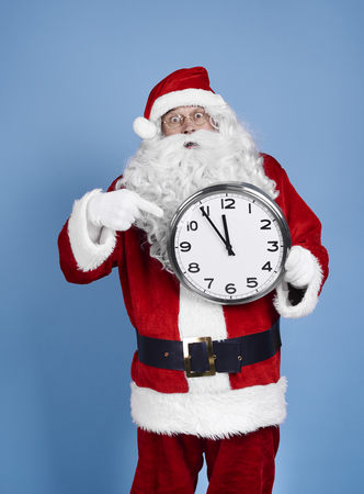 Worried santa claus holding clock
