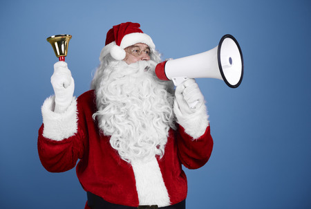 Santa claus with handbell shouting into megaphone