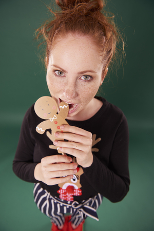 Young woman eating gingerbread man
