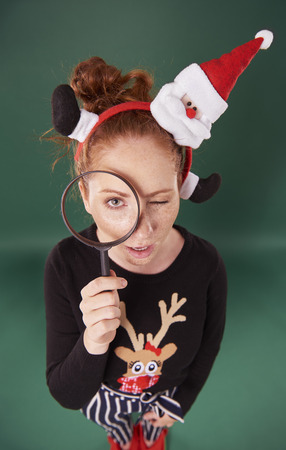 Woman in christmas clothes looking through magnifying glass