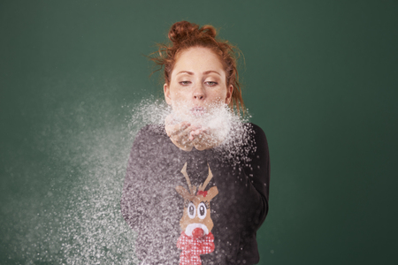 Young woman blowing fake snow