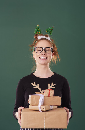 Happy girl holding stack of christmas present