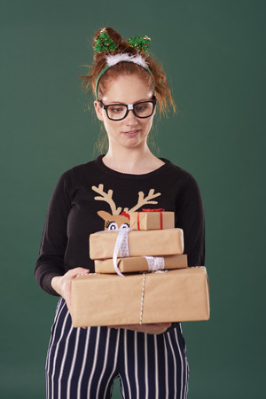 Displeased woman holding stack of christmas present 版權商用圖片