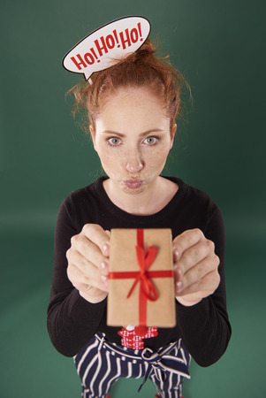 Funny girl showing a christmas present Stock fotó - 110694733