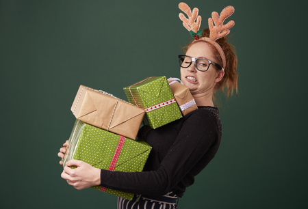 Funny woman carrying stack of christmas gifts 写真素材