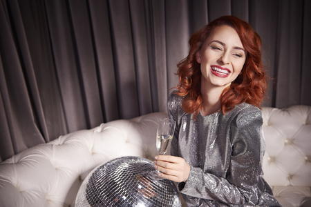 Cheerful woman with champagne and disco ball at night club