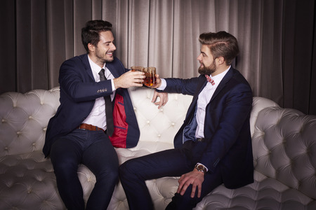 Men with whiskey toasting at entertainment club