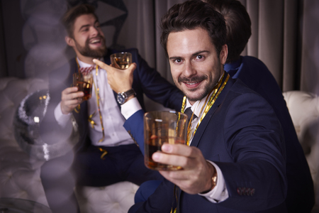 Group of businessmen with whiskey enjoying at night club