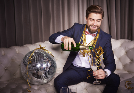 Cheerful man pouring champagne at night club