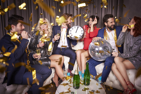 Group of people partying among confetti Stock Photo